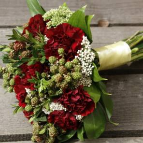 Букет невесты из красных гвоздик и ягодок